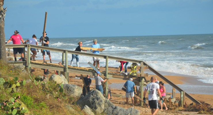 They worked in waves Sunday morning, some 150 volunteers along the Flagler Beach shore, cleaning up the mess Hurricane Matthew left behind so the city's beaches could begin reopening by mid-week, bringing back visitors and residents. Click on the image for larger view. (© FlaglerLive)