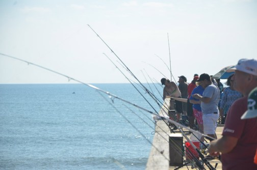 The Flagler Beach Pier's fishermen paid little attention to the ribbon-cutting at the entrance to the structure on Saturday. (© FlaglerLive)