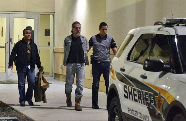 Michael Cummings being led out to a patrol car, on his way to the county jail this evening, flanked by detectives Mark Moy, left, and Jorge Fuentes, who worked the case. (© FlaglerLive)