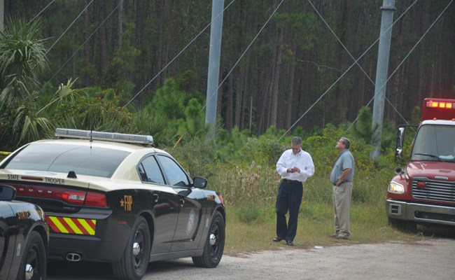 Jay Gardner, Flagler County's property appraiser and a long-time co-owner of the plane that crashed, near the scene of the crash, which was deep in the woods and not accessible except to emergency personnel. (© FlaglerLive)