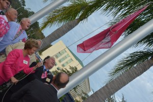 Tax Collector Suzanne Johnston raises the Pink Army Flag amid a platoon of men. (c FlaglerLive)