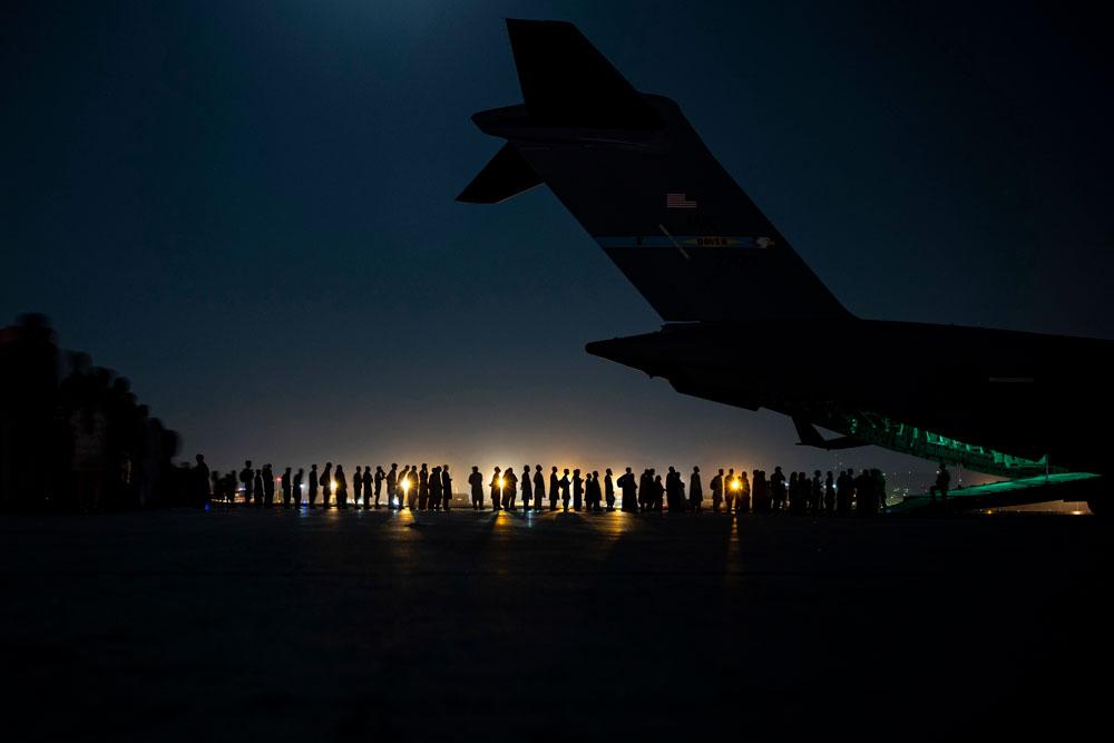 Airmen prepare to load qualified evacuees aboard a U.S. Air Force C-17 Globemaster III aircraft at Hamid Karzai International Airport in Kabul last week. (Taylor Krul/DOD)