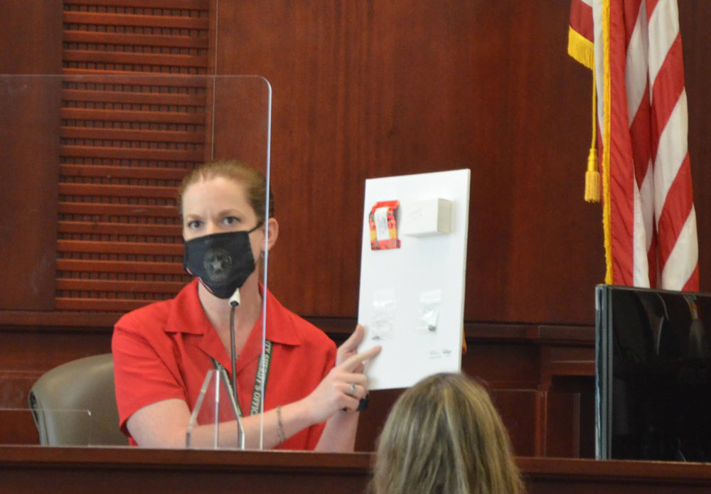 Lanie Rittenour, formerly a crime scene investigator, now a dispatcher with the Flagler County Sheriff's Office, shows the bullet fragments extracted from Elijah Rizvan's body during a brief testimony this morning--a rare moment of straight-forward testimony in a day dominated by three witnesses' fleeing and eluding attorneys' questions. (© FlaglerLive)