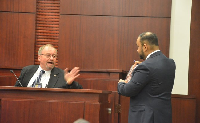 Former FDLE Agent Philip Lindley on the stand, addressing the search warrant he had drafted ahead of a search of then-Supervisor of Elections Kimberle Weeks's office, under questioning from Weeks attorney Kendell Ali. (© FlaglerLive)