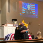 Sheriff Rick Staly hugging Brian Luciano, one of Paul Luciano's children, at the detention deputy's funeral service on Sept. 3. (FCSO)