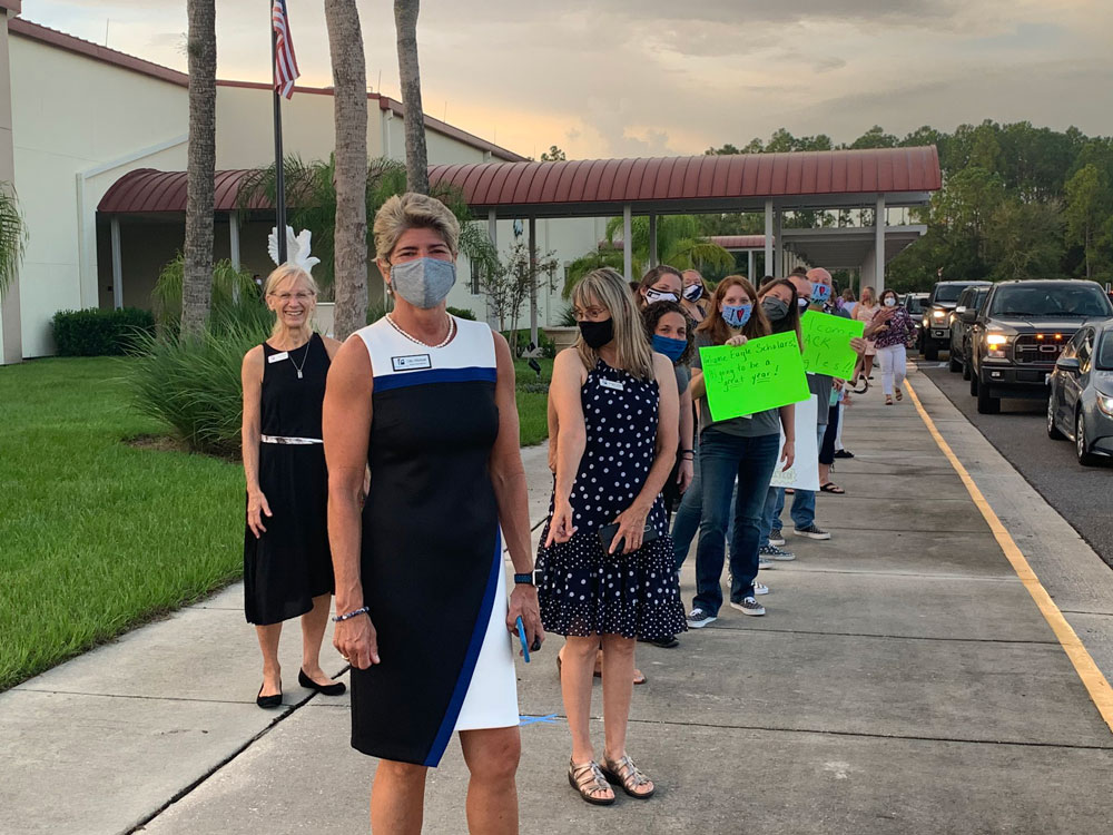 The picture tells the story: Superintendent Cathy Mittelstadt, who visited every school today, led a welcome-back line at Buddy Taylor Middle School, where every faculty member and employee and School Board member Maria Barbosa wore a mask, as per school district regulation--with the exception of School Board Chairman Janet McDonald, who has frequently denied the severity of covid-19 and is not a big mask wearer. (© FlaglerLive)