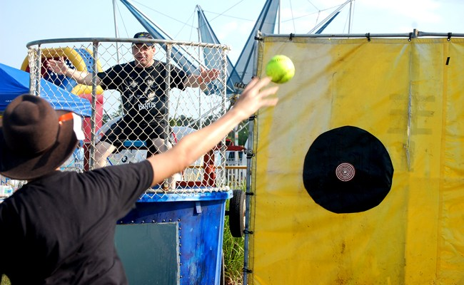 Coounty Commissioner Nate McLaughlin, being a good sport, about to get dunked at Palm Coast's recent Rock 'n Ribfest at Town Center. The pitcher is Alexander Lynn. (© FlaglerLive)