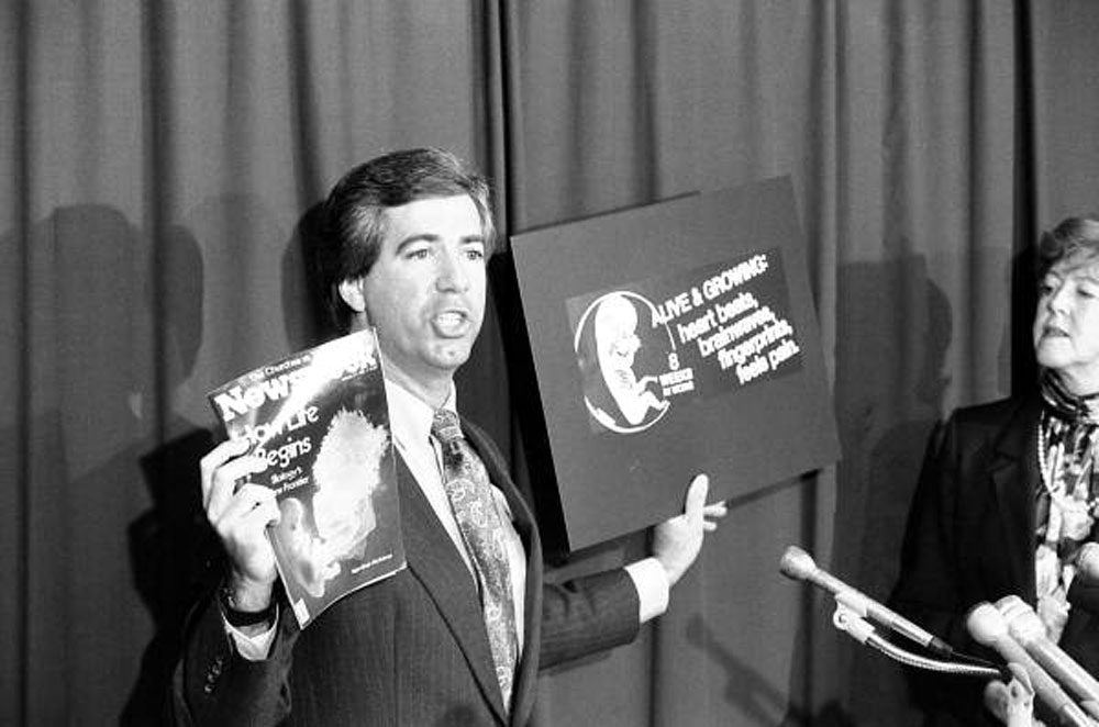 """""""Kenneth Conner, director-at-large for Florida Right To Life, Inc., holds up the cover of Newsweek magazine, left, and pro-life ad graphic barred from 1987 state government telephone directory. Conner held up the comparisons during a Thursday news conference at which the group announced their support of Republican Paula Hawkins for the U.S. Senate."""""""