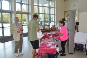 Left, Tony Papandrea, board chairman of the Florida Hospital Foundation, near a stand with Pink Army goodies this morning at the Government Services Building. (c FlaglerLive)