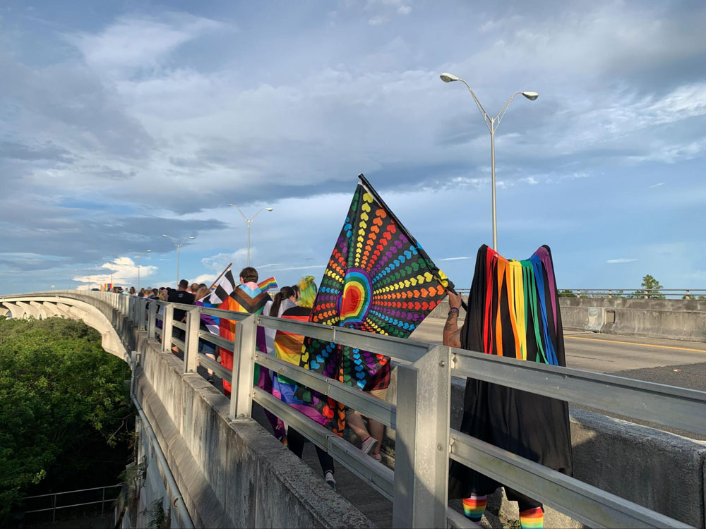 Flagler's second Pride march as it set off over the Flagler Beach bridge Saturday evening, before a vigil at Veterans Park on the other side. (© FlaglerLive)