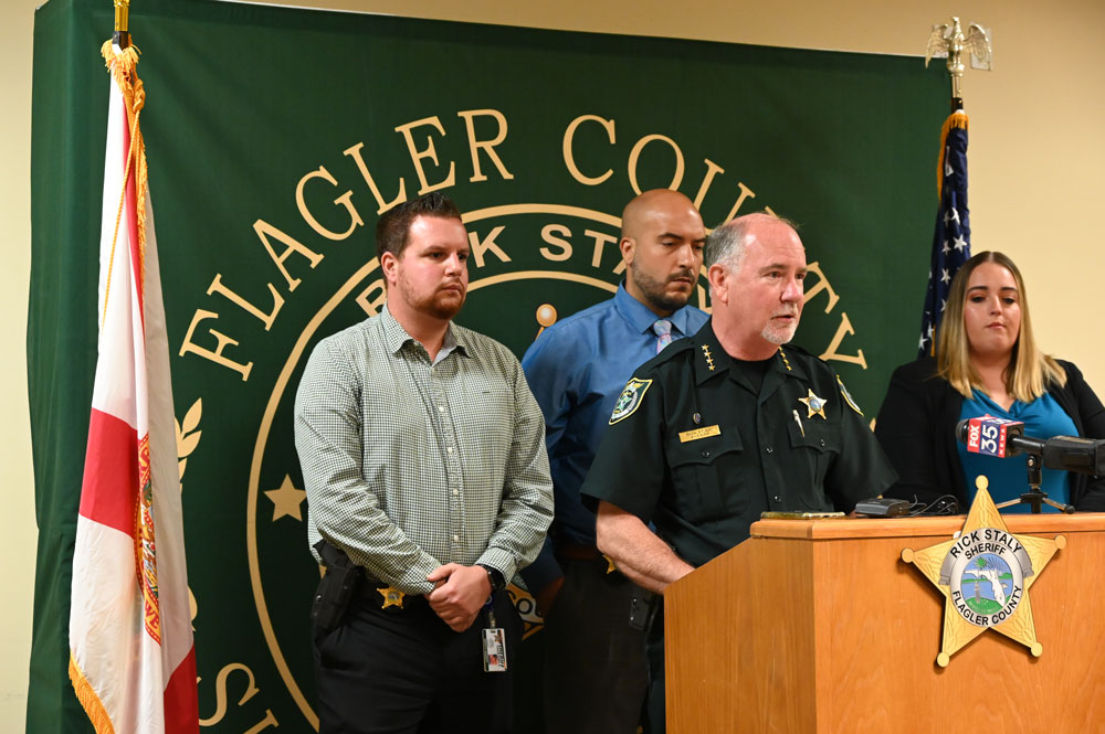 Sheriff Rick Staly announcing the charge against Robert Hill today with the detectives who worked the case. From left, Gabe Fuentes, Augustin Rodriguez, and the lead detective, Sarah (© FlaglerLive)