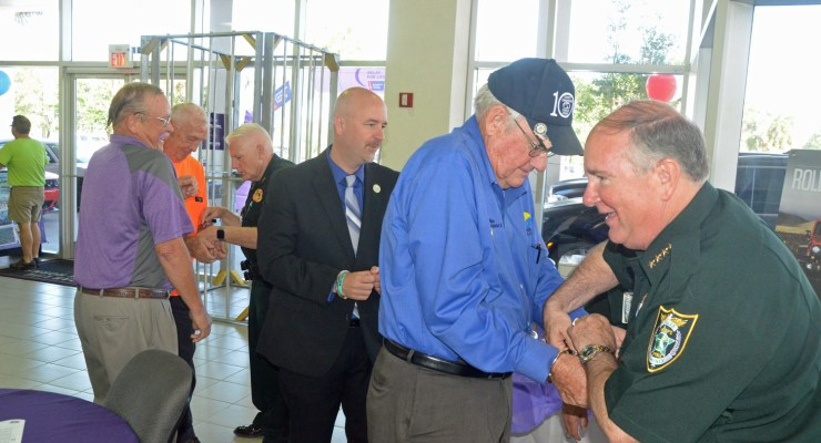 Sheriff Rick Staly takes pity on the men he's just arrested and starts undoing the handcuffs on County Commissioner Dave Sullivan, who'd be followed by Superintendent Jacob Oliva and County Commissioner Charlie Ericksen, who was being assisted by Chief Mark Strobridge. To the left is Steve Canfield, who's leading the Relay for Life fund-raising effort in the county this year, and who had dyed his mustache mauve for the occasion. (© FlaglerLive)