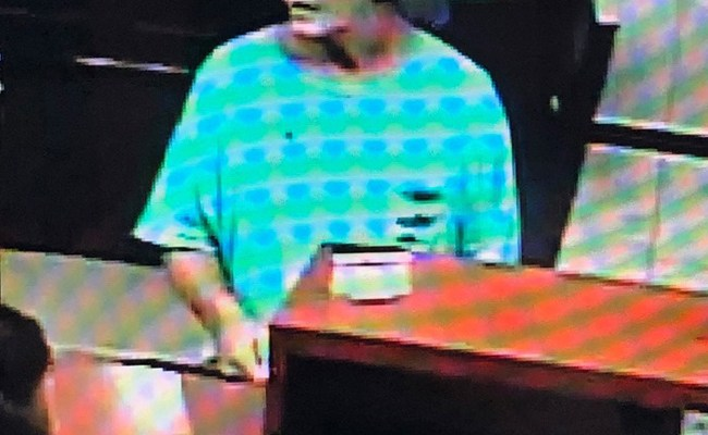 The man believed to be Gary Rahme at Ameris Bank on July 12 as a teller apears to be preparing a bag of money for him. The image was released by the St. Johns County Sheriff's Office.