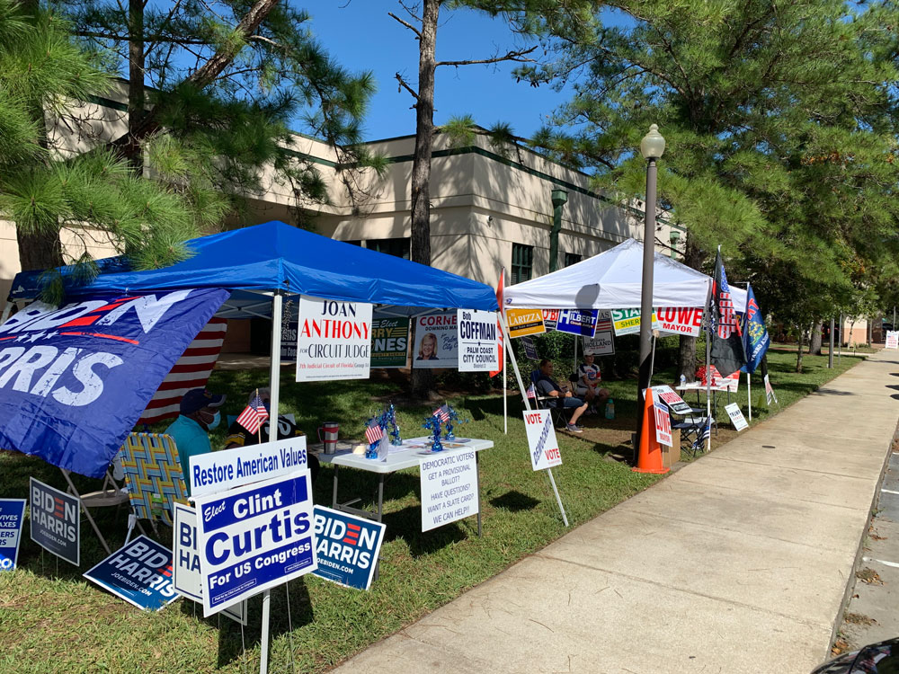 Competing tents at the Flagler County Public Library, one of three early voting sites. (© FlaglerLive)
