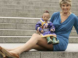 He Pingping from Inner Mongolia, the world's smallest man, sits on the lap of Svetlana Pankratova from Russia