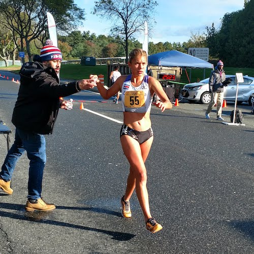 A female race walker accepts some water during the US 30K Race Walking National Championships in Long Island, NY, in October 2018.