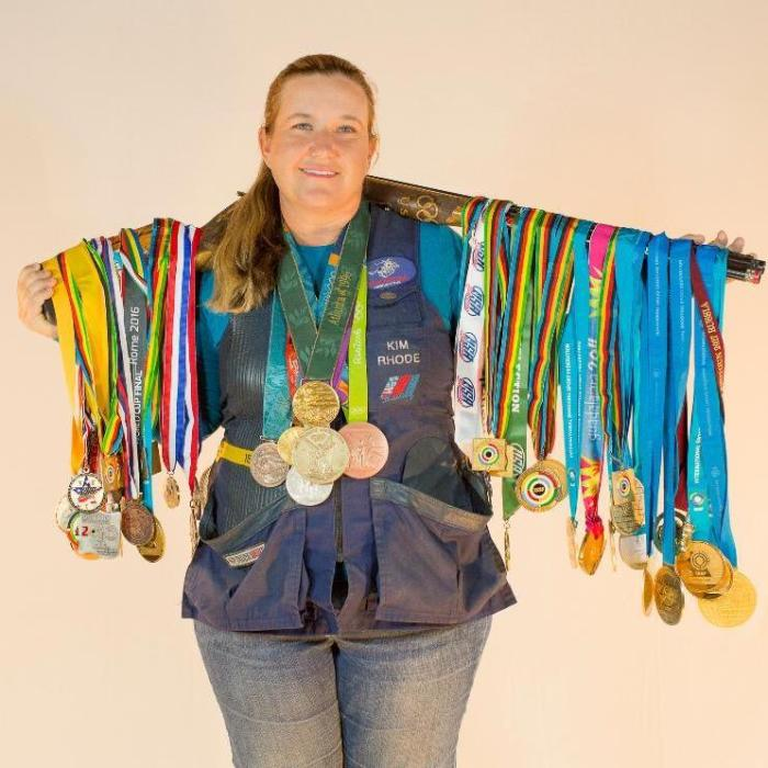 6x Olympic shotgun shooter Kim Rhode displays her vast collection of medals. Her gun is slung around her shoulders, with medals hanging off the gun. Several medals are also draped around her neck.