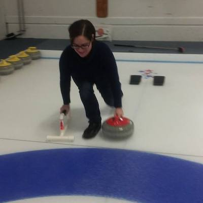 """Alison Brown, co-host of """"Keep the Flame Alive,"""" the podcast for fans of the Olympics and Paralympics, throws a curling stone at Nutmeg Curling Club."""