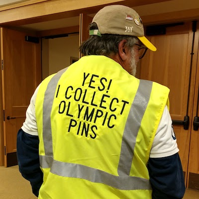 """Olympic pin collector Ed Schneider models his bright yellow vest that says, """"Yes! I collect Olympic pins""""."""