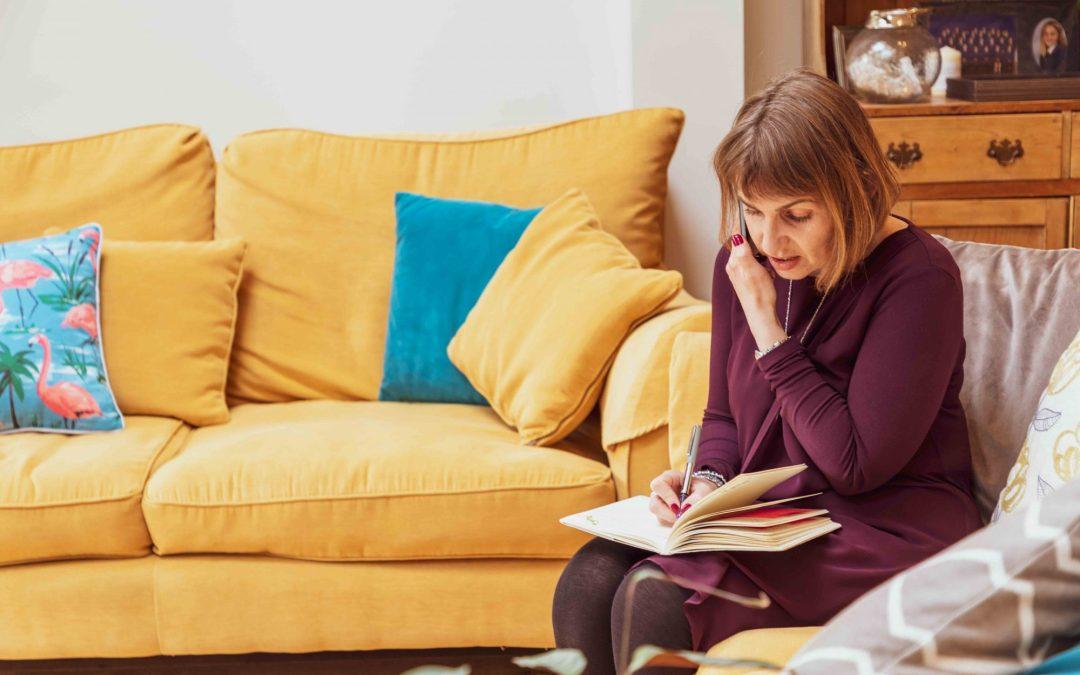 Sarah on phone writing in diary