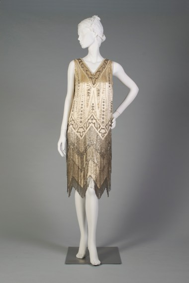 American, ca. 1920-1929. Dress decorated with beads and pearls with a zig-zag hem.