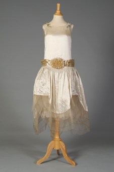 American, ca. 1928. This is a wedding dress, typical of the 1920s it is not floor length and has the addition of artificial orange blossoms on the belt and shoulders.