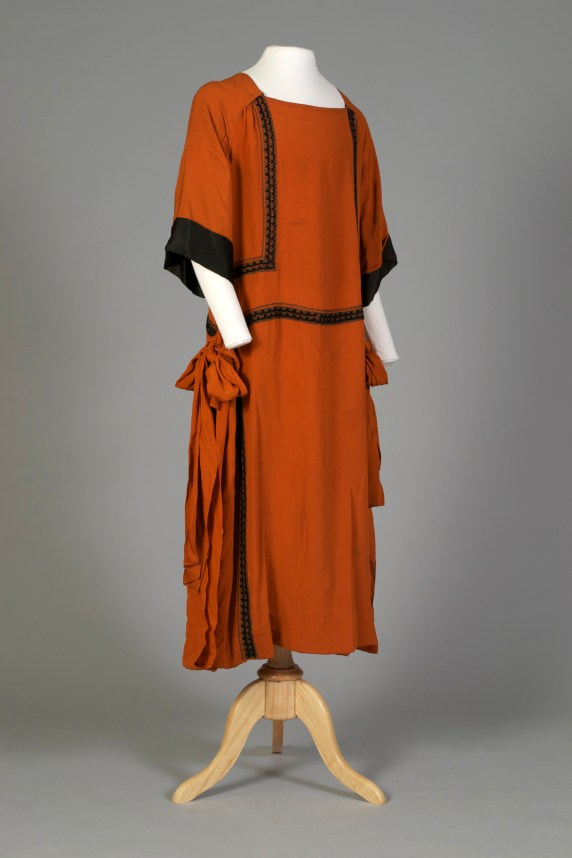 American, ca. 1925-1929. Rust colored silk crepe dress with black trim, black and gold machine embroidered stitching, ties on side, three snaps at each side of collar.