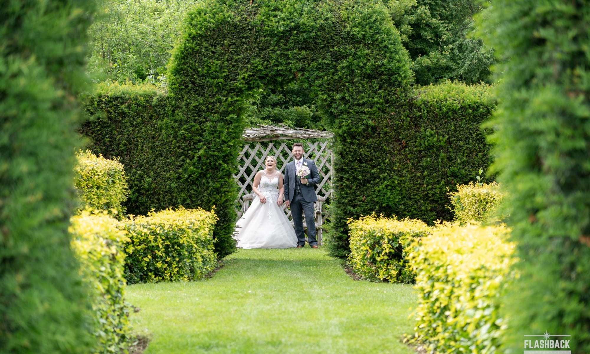 the Secret Gardens - Yalding-Maidstone-Kent - Bride and Groom walking through hedged archway with groom holding the flowers located in our Kent Wedding Gallery
