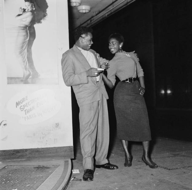 A young couple pose outside the 'Club Americana', a Saturday night jazz club open from midnight until 7 a.m., London, 25th November 1955. (Photo by Keystone Features/Hulton Archive/Getty Images)
