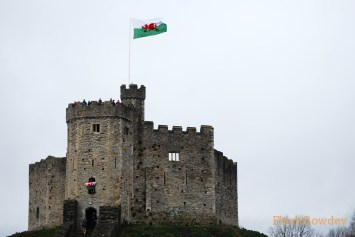 Excited residents wave Welsh flags out of the windows of Cardiff Castle