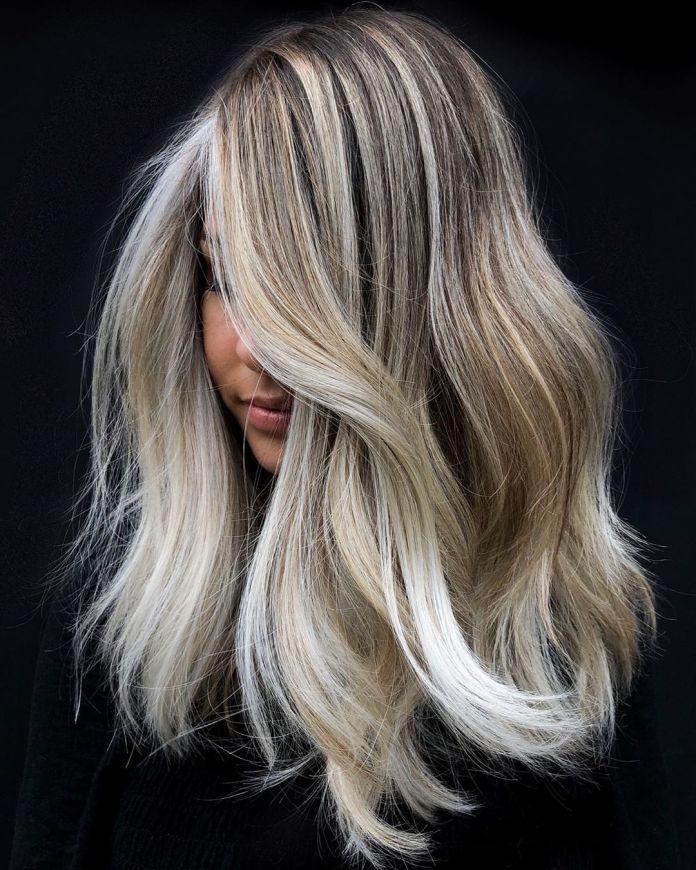 Balayage avec des racines foncées et des reflets blonds blancs