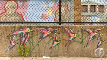 Street art depicting a flock of colorful birds can be seen across the street from Pat's King of Steaks in the Italian Market neighborhood of South Philadelphia, PA.