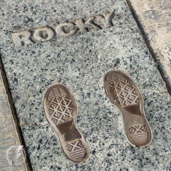 "An inlay impression at the top of the Rocky Steps, in Philadelphia, PA of the Converse sneakers that Sylvester Stallone wore in the movie ""Rocky"" was installed to replace the Rocky statue created by A. Thomas Schomberg in 1982 which was installed for the filming of ""Rocky III"". After filming was complete, a debate arose between the Art Museum and Philadelphia's Art Commission over the meaning of ""art"". City officials, who argued that the statue was not ""art"" but a ""movie prop"", and it was eventually moved to a grassy area at the base of the stairs."