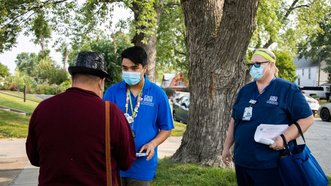 Eddie Nunez and Mary McConnaughey, employees of One World Community Health Centers, talk to a passerby as they go door-to-door in a South Omaha neighborhood, offering residents the COVID-19 vaccine.