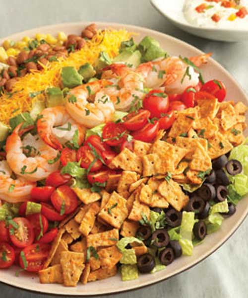 Recipe for Rainbow Mexican Salad - Colorful and flavorful ingredients like tomatoes, Cheddar cheese, avocado, corn and olives are easily arranged to make a salad that gets a delicious crunch from crumbled cheese crisps. It makes a beautiful presentation and is ready in just 30 minutes.