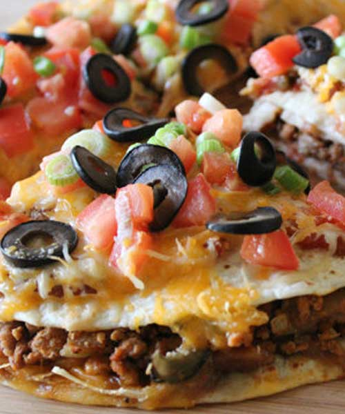 A tasty and easy Mexican-style pizza – delicious corn tortillas topped with beans, beef and all the delicious taco toppings you can imagine!
