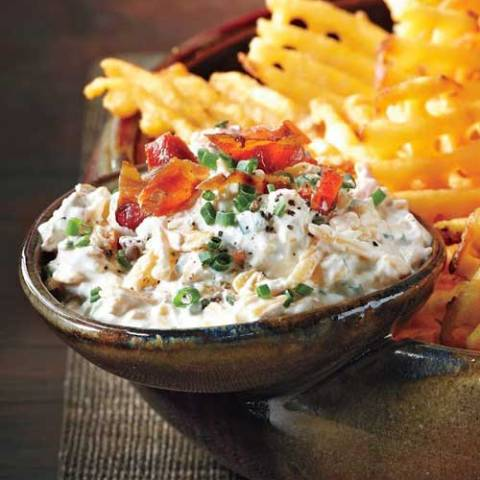 Recipe for Loaded Baked Potato Dip - Use extra-crispy waffle fries as dippers in this delicious concoction and don't forget the crumbled bacon and hot sauce!