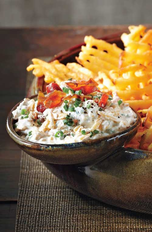 Use extra-crispy waffle fries as dippers in this delicious Loaded Baked Potato Dip and don't forget the crumbled bacon and hot sauce!