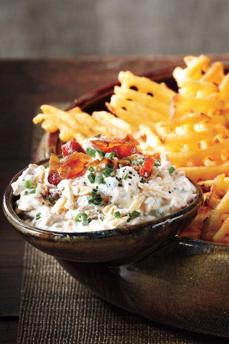 Use extra-crispy waffle fries as dippers in this delicious Loaded Baked Potato Dip and don't forget the crumbled bacon and hot sauce! #dip #appetizer #partyfood