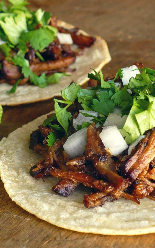 Recipe for Tacos De Barbacoa - Good barbacoa is succulent beef that is slow-simmered in a spicy broth flavored with tangy lime juice, smoky chipotle chiles and plenty of garlic until it's practically falling apart.
