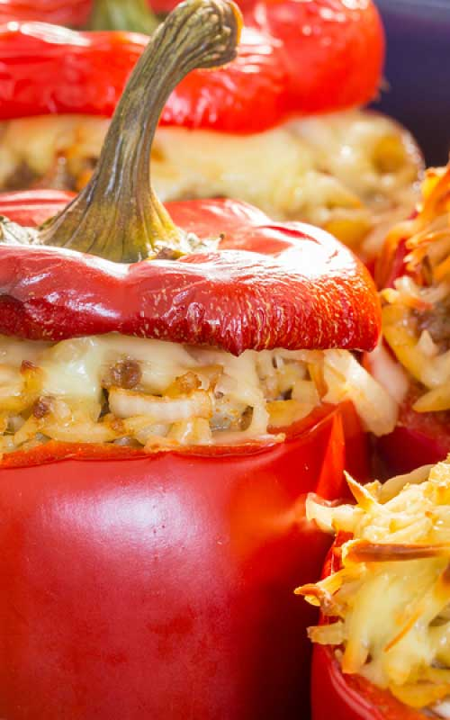 Here is a recipe for meatless Rice Stuffed Red Peppers. Instead of meat, you have fresh mushrooms, onion, rice and two types of cheese. #stuffedpeppers #meatlessmonday #dinnerideas