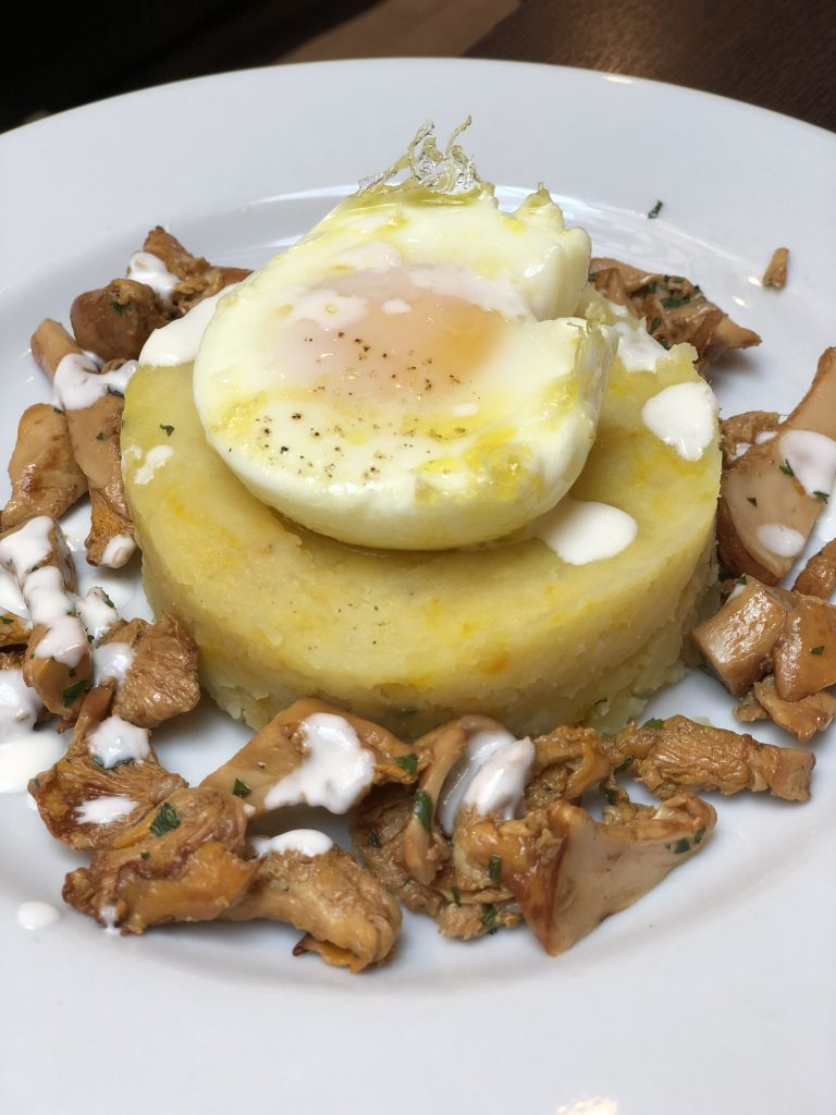 poached egg on a tartlet of potatoes with saffron pistils and a Parmesan fondue