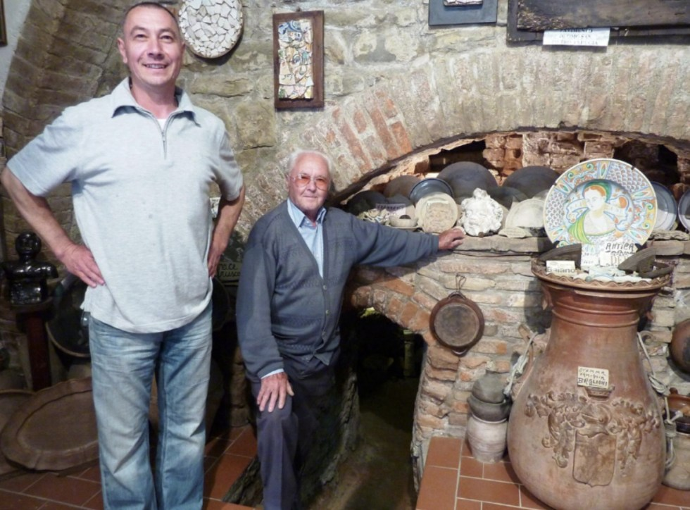 Giovanni and his father standing in front of the ancient kilns discovered in their pottery shop