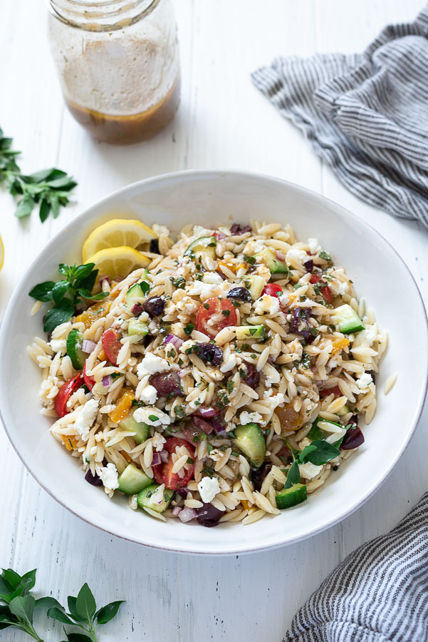 front shot of greek orzo salad in a serving bowl with lemon slices and oregano garnishes