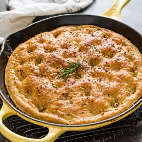 close up of one hour focaccia bread in skillet with rosemary on top