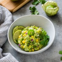 Mango tomatillo guacamole in white bowl with lime and cilantro