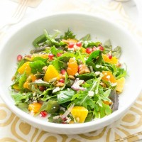 Golden beet and orange salad in white bowl with pomegranate on top