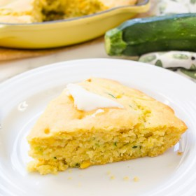 front shot of a slice of zucchini cornbread on a white plate