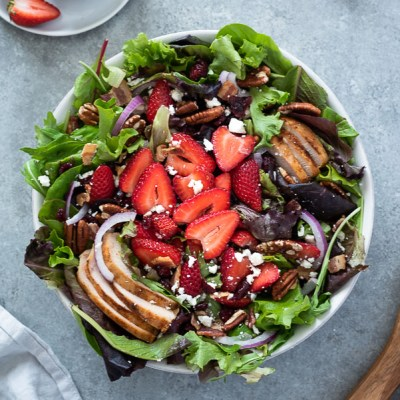 overhead shot of strawberry fields salad in white serving bowl with wooden servers