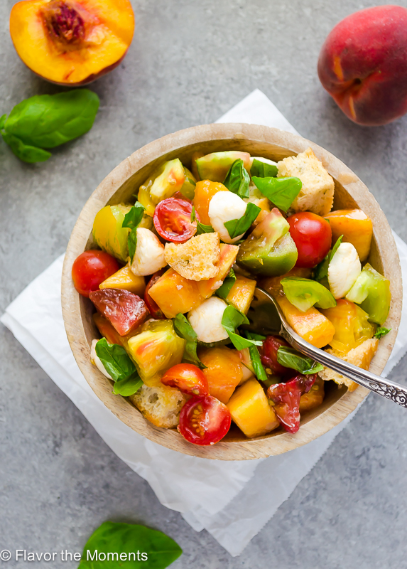 Heirloom Tomato and Peach Caprese Panzanella Salad is colorful heirloom tomatoes and juicy peaches tossed with basil, mozzarella, and homemade croutons. It's the perfect summer salad recipe! @FlavortheMoment